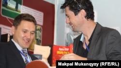 Участник книжной выставки, представитель китайской компании Worldwide Printing Solutions Аркадий Корниенко (справа). Алматы, 11 апреля 2013 года.