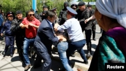 Riot police officers detain demonstrators during a protest against proposed government land reforms in Almaty on May 21.
