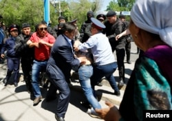Жер митингісіне шықпақ болған азаматтарды ұстап жатқан полицейлер. Алматы, 21 мамыр 2016 жыл.