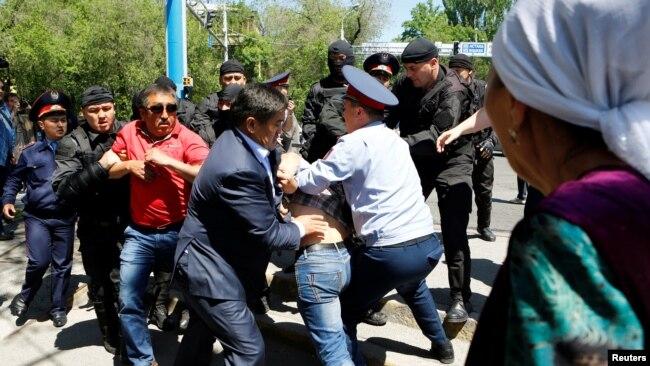 Полицейские задерживают протестующих в Алматы 21 мая 2016 года.