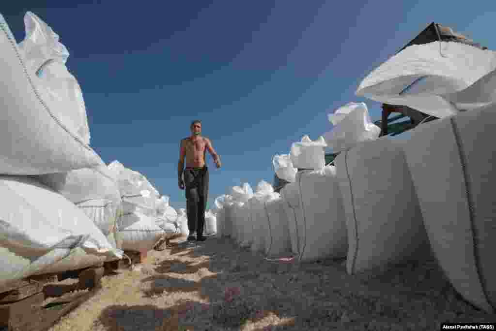 A worker walks alongside bags filled with salt.