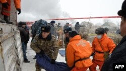 KYrgyzstan -- Servicemen and rescuers carry a body bag with a victim at the crash site of a Turkish cargo plane in the village of Dacha-Suu outside Bishkek, January 16, 2017