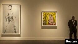 """Një roje rri afër pikturave të Endi Uarholit, """"Elvisi i Dyfishtë"""" dhe të Roj Lihtenshtajni, """"vajza e Fjetur"""", Nju Jork, prill, 2012"""