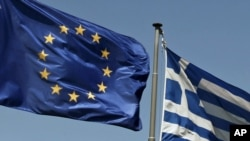 The European Union and Greek flags fly above the Parthenon in Athens.