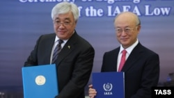 Kazakh Foreign Minister Erlan Idrisov (left) and Yukiya Amano, head of the IAEA, pose after signing an agreement to establish a bank of low-enriched uranium in Kazakhstan on August 27.