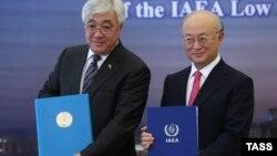 یوکیا آمانو (راست) در کنار ارلان ادریسوف، نخست وزیر قزاقستان، پس از امضای قرارداد بانک سوخت اتمی