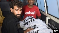 Abdul Majeed (left), brother of Shafqat Hussain, sits beside Hussain's body in an ambulance after his execution in Karachi on August 4.