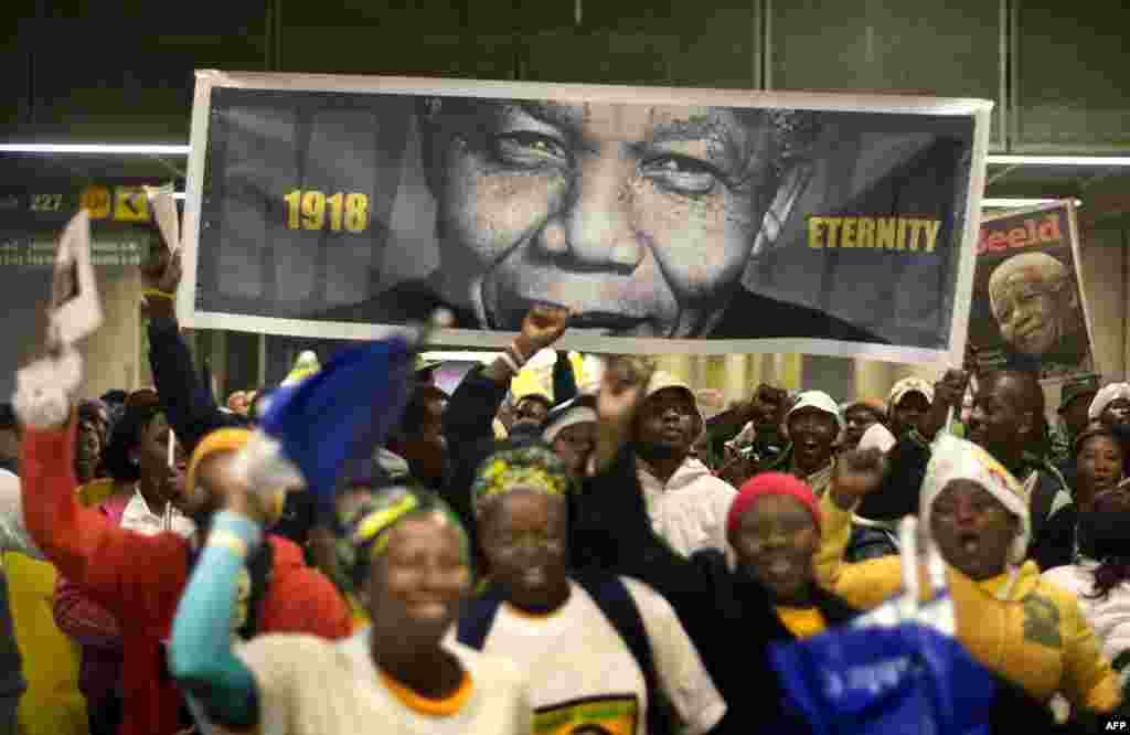 People arrive at the First National Bank (FNB) Stadium, also known as Soccer City, ahead of the national memorial service for late President Nelson Mandela in Johannesburg.