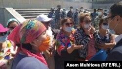 На фоне сотрудников спецподразделения МВД многодетные матери в масках обращаются к чиновнику касательно жилищной программы. Нур-Султан, 2 июня 2020 года.