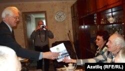 Татарстан язучылар берлеге рәисе Рәфис Корбан Рим Идиятуллинга бүләк тапшыра