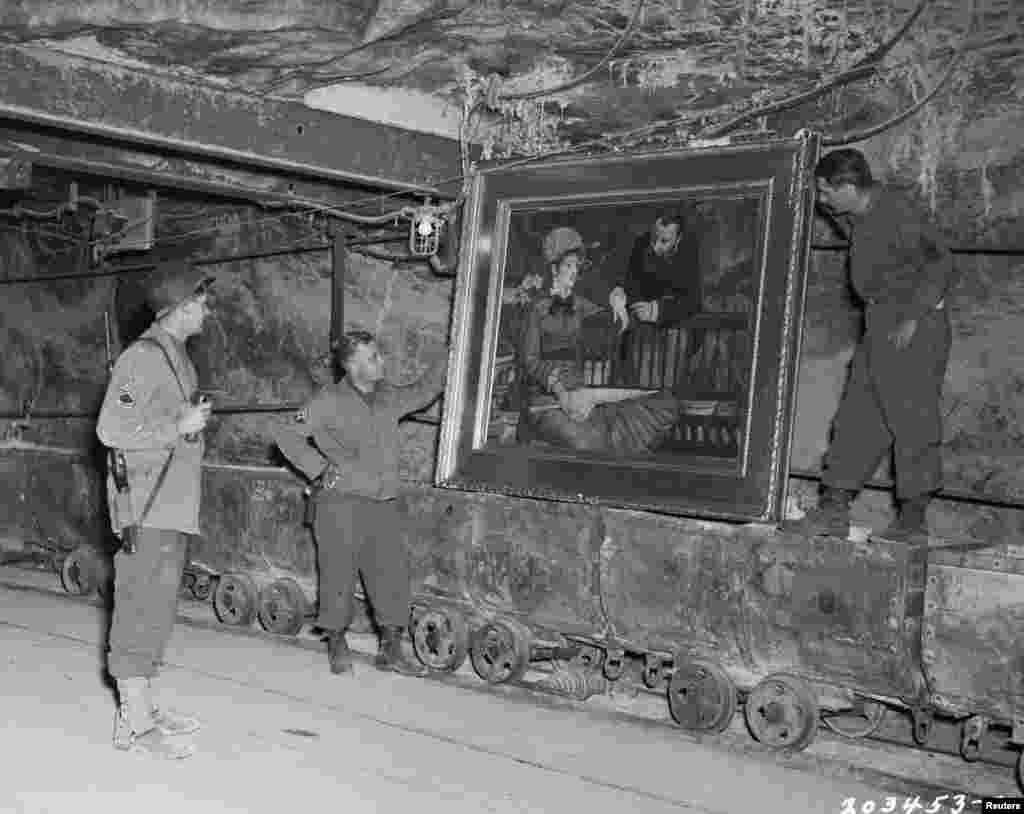 "U.S. soldiers examine the painting, ""Wintergarden,"" by French Impressionist painter Edouard Manet. It was stolen by the Nazi regime and hidden in a salt mine in central Germany. The artwork was recovered in 1945 and was not among those discovered in the Munich apartment in 2012."