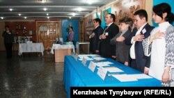 Члены избирательной комиссии исполняют гимн Казахстана во время начала голосования на избирательном участке №263. Алматы, 15 января 2012 года.