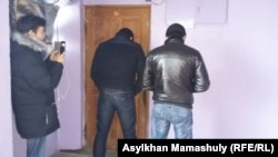 Полицейские, стоящие спиной, блокируют дверь в офис редакции оппозиционного сайта Nakanune.kz, где в это время происходит обыск. Алматы, 18 декабря 2015 года.