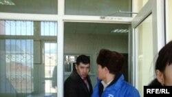 """Жол полициясы басқармасына күштеп әкелінген """"Алға"""" партиясының белсендісі Ғазиз Сайфолла (ортада) және қалалық ішкі саясат бөлімінің бастығы Есенжан Керіков (сол жақта). Атырау, 25 ақпан 2009 ж."""