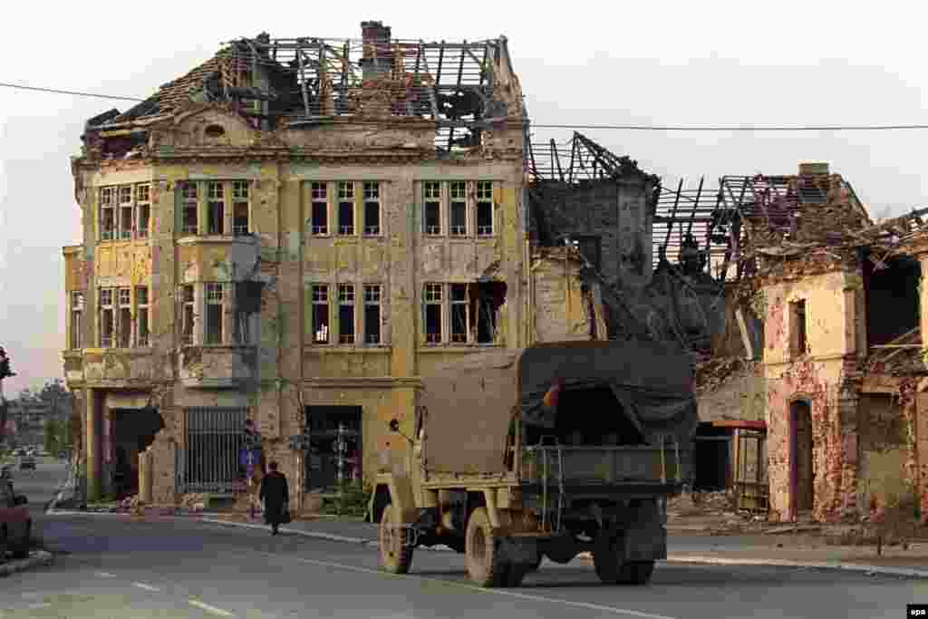 A lorry passes a ruined house, 23 October 1992.Vukovar is now a part of the self-proclaimed Srpska Krajina -- a Serb enclave in Croatia.