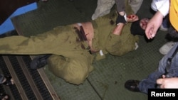 Ізраїльський спецназівець у руках пропалестинських активістів під час десанту на судно 31 травня 2010 року