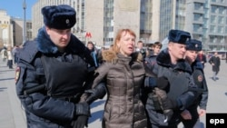 Russian police detain a protester ahead of an opposition rally in central Moscow.