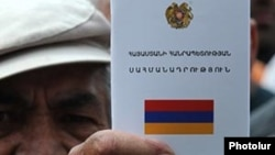 A protester holding an Armenian constitution, undated