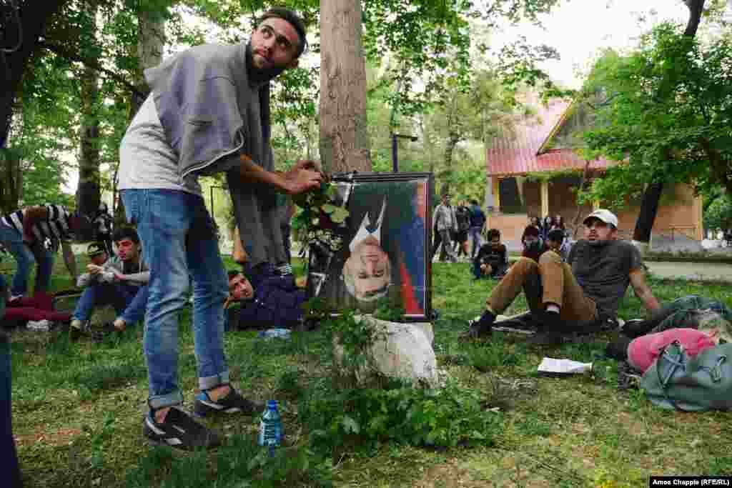 A man places a flower onto an upside-down portrait of Prime Minister Serzh Sarkisian in a children's park in Yerevan. The frame features a black strip of cloth at the corner, traditionally placed over a portrait when someone is dead.