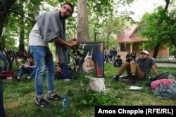 A young man places a flower onto an upside-down portrait of Prime Minister Serzh Sarkisian in a children's park in Yerevan. The frame features a black strip of cloth at the corner, traditionally placed over a portrait when someone is dead.