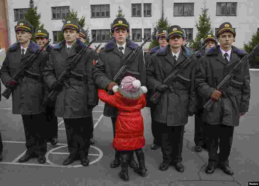 A girl hugs her brother, a recruit from the presidential regiment, as he takes the oath at a military base in Kyiv. (Reuters/Gleb Garanich)