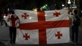 26-njy iýunda daňdan Tbiliside, parlament binasynyň golaýynda protestçiler gürji baýdagyny göterip barýar.
