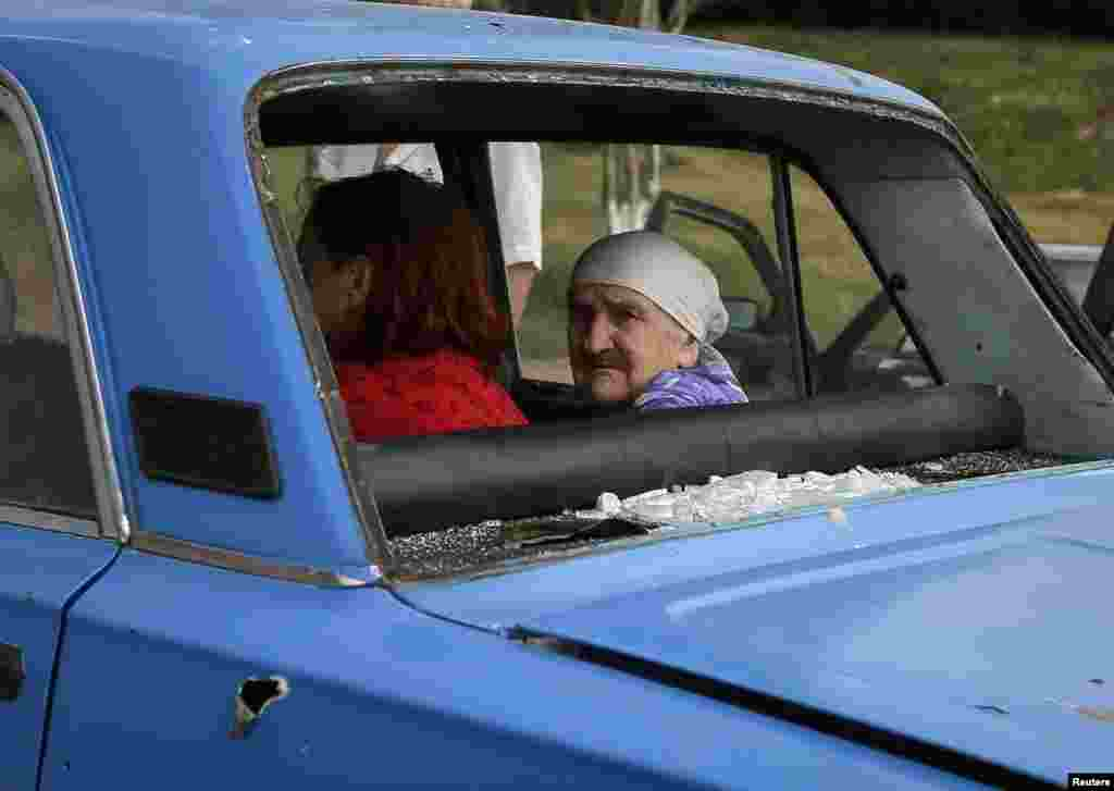 An old woman looks from inside a car with bullet holes and shattered windows as she flees fighting in the eastern Ukrainian town of Slovyansk on June 9. (Reuters/Gleb Garanich)