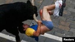 Бык поддевает на рога одного из участников бега на фестивале святого Фермина в Памплоне, 11 июля 2013 года.