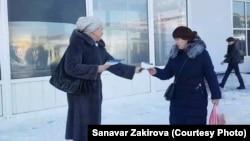 Алматы тұрғыны Санавар Закирова өзі құрған партияның үнпарақтарын таратып жүр.