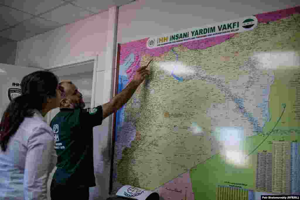The head of the IHH facility shows a journalist a map of camps they operate inside Syria.