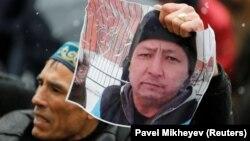Мужчина с портретом активиста Дулата Агадила на траурной акции в Алматы. 28 февраля 2020 года.
