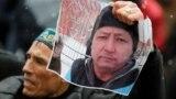 Наразылық шарасы кезінде белсенді Дулат Ағаділдің суретін ұстап тұрған адам. Алматы, 27 ақпан 2020 жыл. Көрнекі сурет.