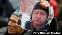 A man holds a photo of Kazakh activist Dulat Aghadil during a commemoration meeting in Almaty on February 27.