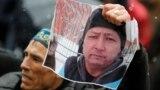 Белсендіні еске алуға арналған азалы акцияда Дулат Ағаділдің суретін ұстап тұрған адам. Алматы, 28 ақпан 2020 жыл.