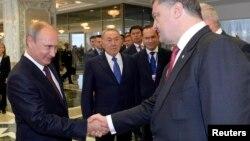 Russian President Vladimir Putin (left) shakes hands with Ukrainian President Petro Poroshenko ahead of talks in Minsk on August 26.