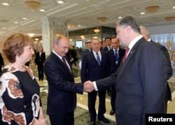 В центре: президент России Владимир Путин и президент Украины Петр Порошенко обмениваются рукопожатием перед началом переговоров. Минск, 26 августа 2014 года.