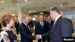 Petro Poroshenko (djathtas) duke u përshëndetur me Vladimir Putinin, në prani të zyrtares së lartë të BE-së Catherine Ashton