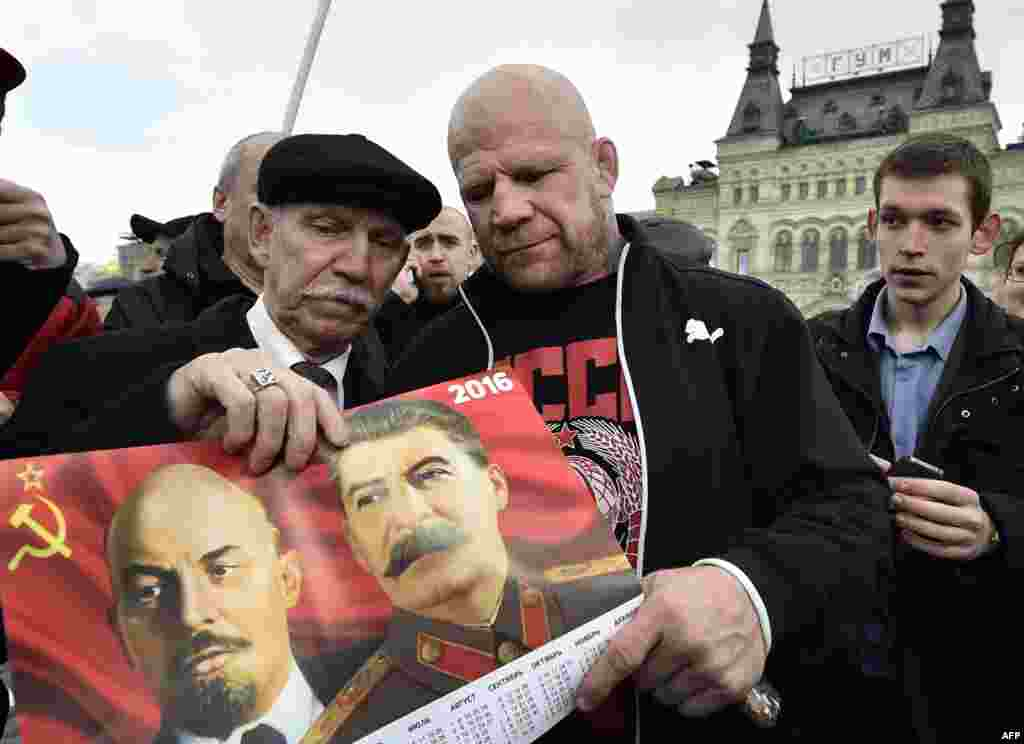 U.S.-born mixed martial arts fighter Jeff Monson (center) holds a picture of Lenin and Stalin as he attends a wreath-laying ceremony to mark the 146th birthday of Soviet state founder Vladimir Lenin at his mausoleum in Red Square in Moscow on April 22. Monson was granted Russian citizenship last year. (AFP/Yuri Kadobnov)