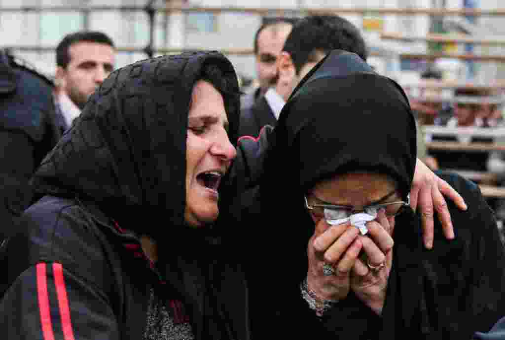The mother of Balal, left, and the mother of Abdollah, the victim, cry together.