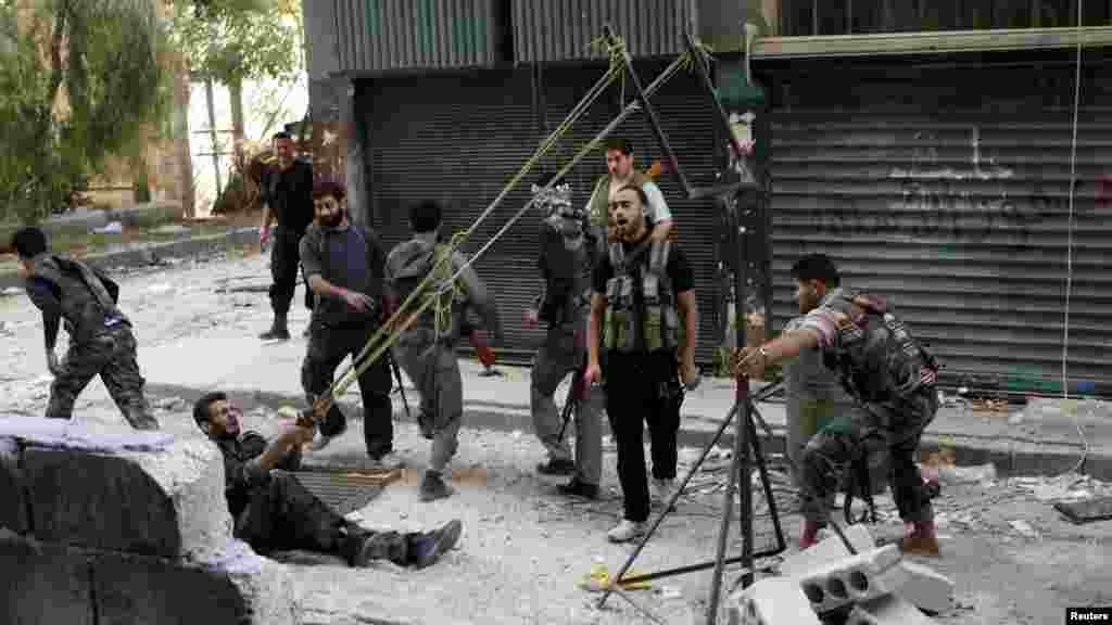 Members of the rebel Free Syrian Army use a catapult to launch a homemade bomb during clashes with pro-government soldiers in the city of Aleppo on October 15. (REUTERS/Asmaa Waguih)