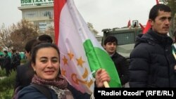 Журналистка Радио Озоди держит в руках флаг Таджикистана