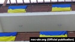 Украінскія сьцягі з чорнымі стужкамі на бальконах нумароў украінскіх атлетаў