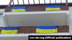 Чорныя стужкі на ўкраінскіх сьцягах у Алімпійскай вёсцы