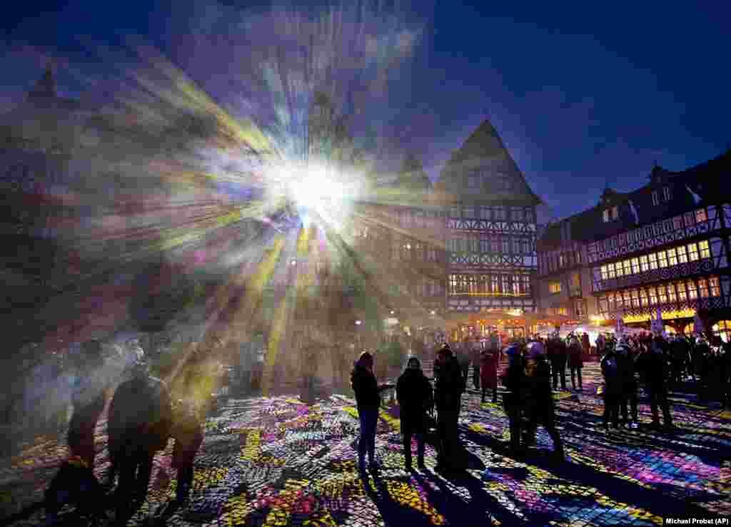 "Germaniýanyň Frankfurt şäherinde ""Luminale"" yşyk festiwalynyň açylyş dabarasy bolan mahaly, Roemer meýdançasyndaky bir jaýdan öwşün atýar. (AP/Michael Probst)"