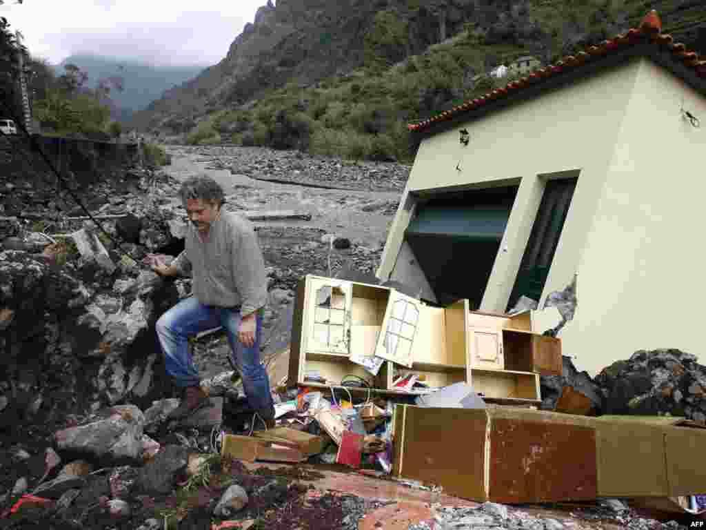 Партугалія, востраў Мадэйра: чалавек каля парэшткаў разбуранага паводкай дома.