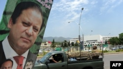 A Pakistani Army vehicle drives past a poster of Prime Minister Nawaz Sharif in Islamabad.