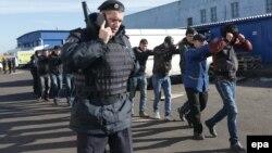 Полицей заңсыз мигранттарды әкетіп барады. Мәскеу, 14 қазан 2013 жыл. (Көрнекі сурет)