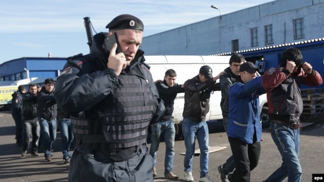Police officers detain alleged illegal migrants at a raid on a warehouse in the Biryulyovo-Zapadnoye district of Moscow on October 14.