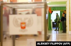 A serviceman guards the entrance to a polling station in Donetsk during voting on November 11.