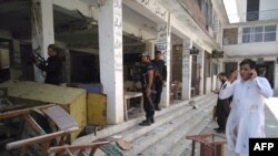 Pakistani police officials inspect the site of a suicide bomb attack at a district court in Mardan on September 2.